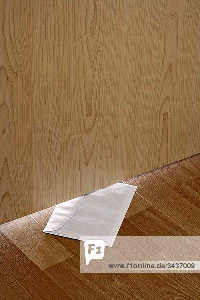 Weiße Umschlag mit Nachricht rutschte unter Holztür