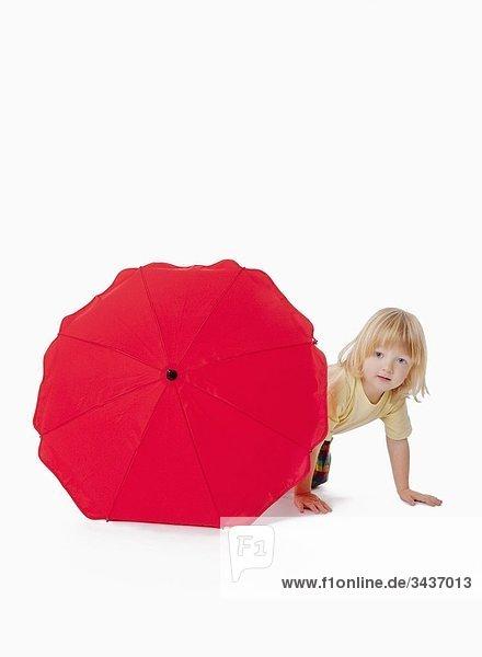 Boy mit langen blonden Haaren spielen mit einem rot Schirm