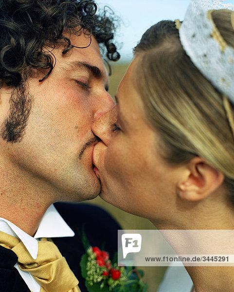 Skandinavien  Schweden  Oland  Braut und Bräutigam küssen  Nahaufnahme
