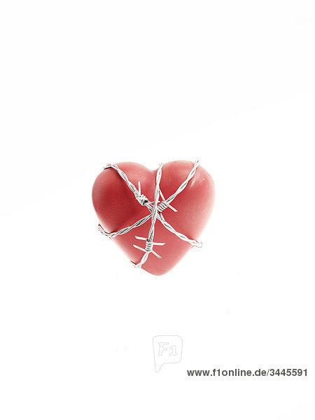 Stacheldraht um einem roten Herz.