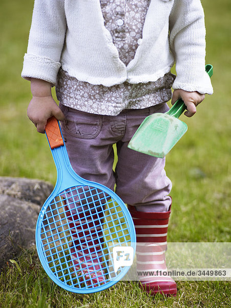 Scandinavia  Sweden  Girl holding toy spade and badminton  close-up  low section