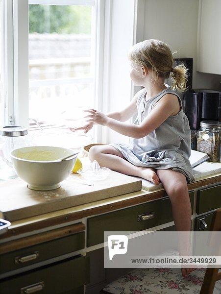 Skandinavien  Schweden  Mädchen essen in Küche zubereiten  Blick aus Fenster