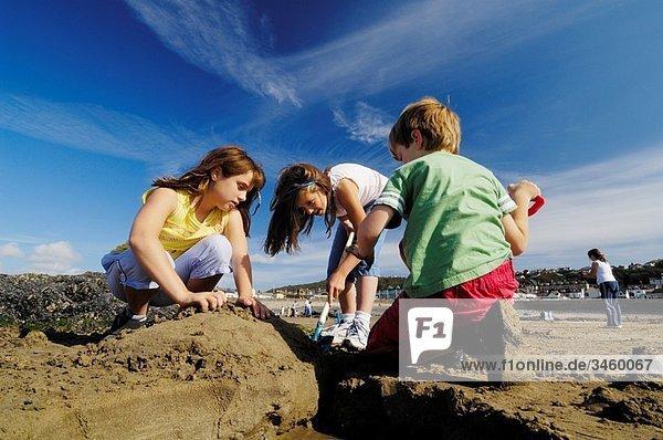 Three preteen children playing in the sun on the beach at Westward Ho in Devon England