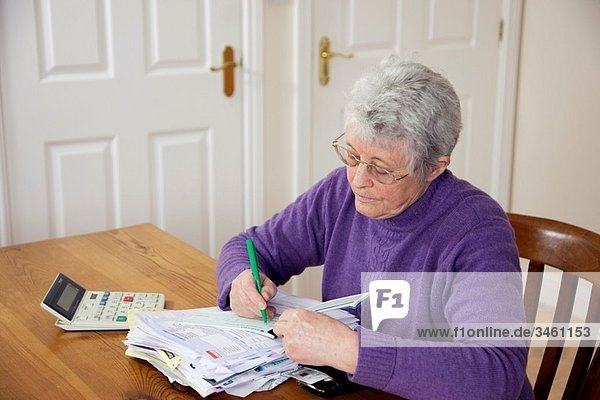 Britain  UK  Europe Senior woman pensioner with a big pile of bills on the table writing a cheque to pay