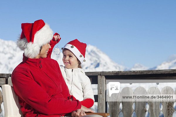 Mother and dauhter wearing Santa hats  playing