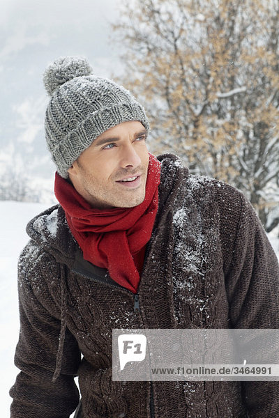 Portrait of young man in winter clothes looking away