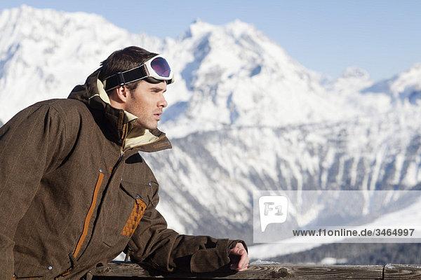Junger Mann in Skikleidung Tagträumen