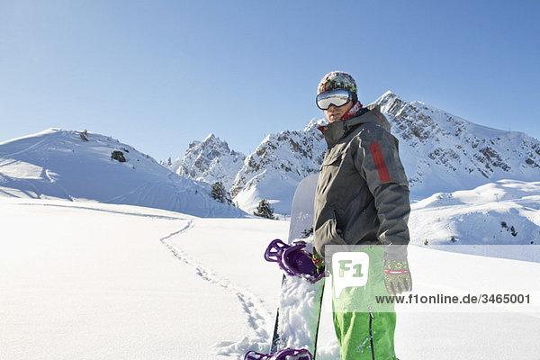 Junger Mann mit Snowboard im Schnee