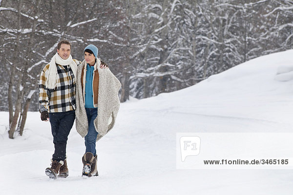 Junges Paar umarmend  im Schnee spazieren gehend