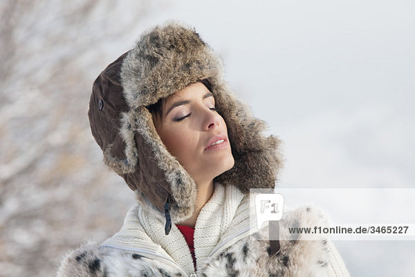 Young woman in winter clothes with eyes closed