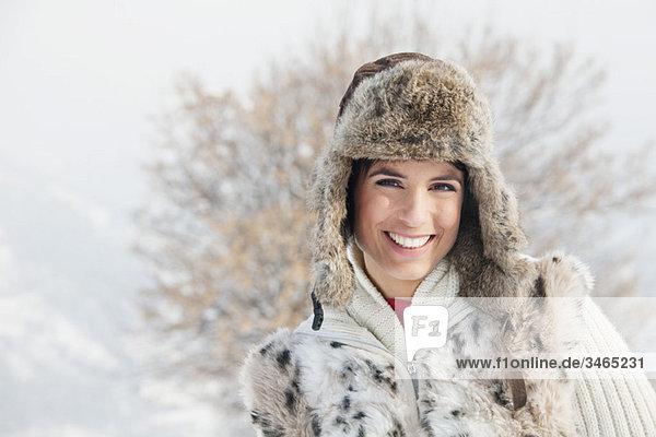 Junge Frau in Winterkleidung lächelnd vor der Kamera