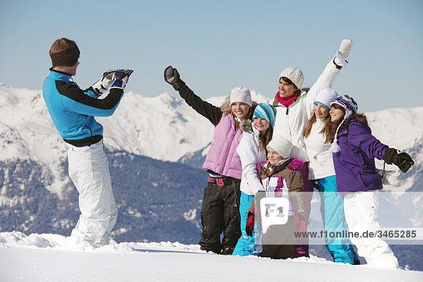 Mann fotografiert Familie im Schnee