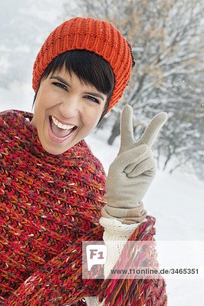 Junge Frau in Winterkleidung macht Friedenszeichen