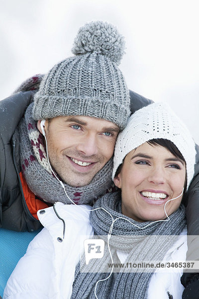 Young couple in winter clothes  listening to music together