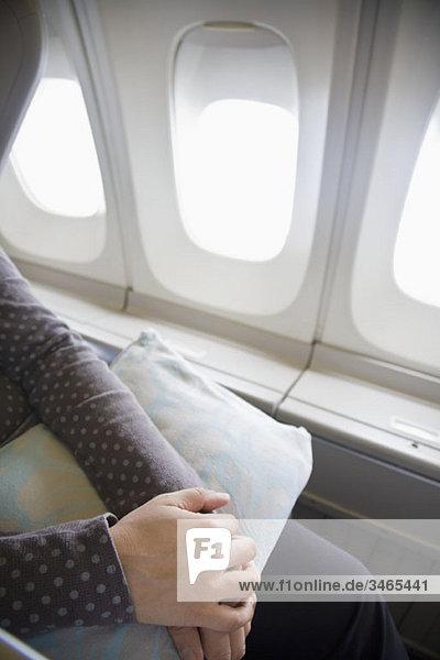 Detail einer Frau,  die mit einem Kissen auf einem Flugzeug sitzt.