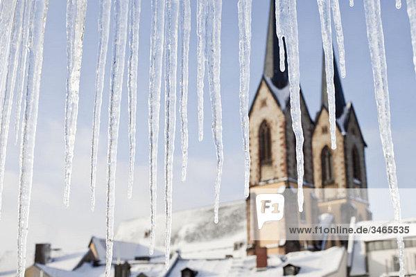 Detail von Eiszapfen und einer Kirche im Hintergrund Detail von Eiszapfen und einer Kirche im Hintergrund