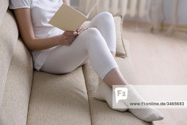Eine Frau  die auf einer Couch mit einem Buch liegt und sich auf den unteren Teil konzentriert.
