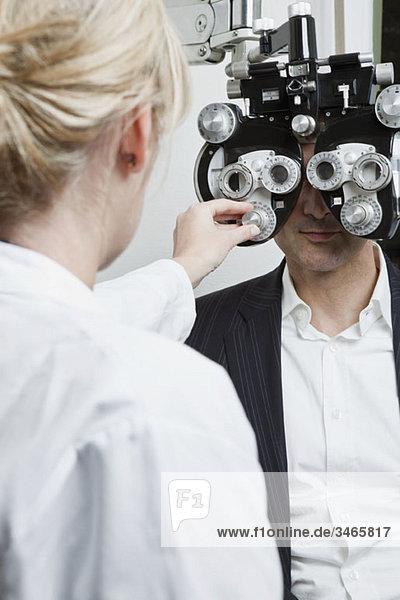 An optometrist conducting an eye exam on a man
