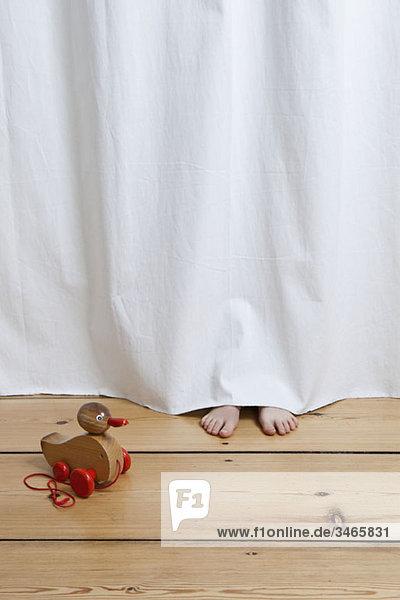 Ein versteckter Kinderfuß  der unter einem hängenden Laken hervorragt.