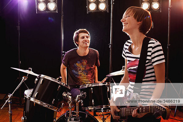 A man playing drums and a woman playing guitar in a rock band performing on stage