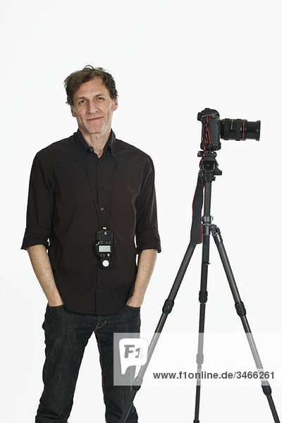 A photographer posing next to his camera on a tripod