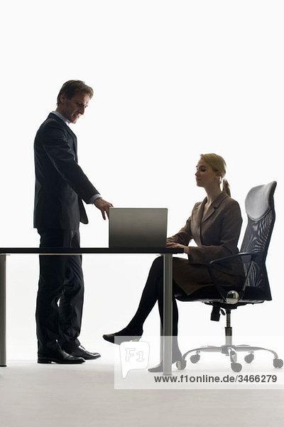 Eine Geschäftsfrau und ein Geschäftsmann  die mit einem Laptop zusammenarbeiten.