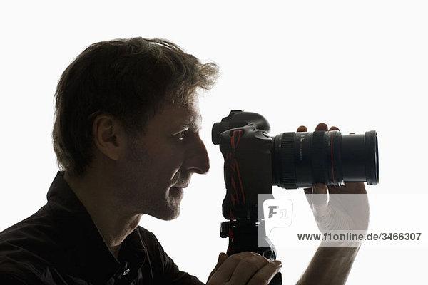 Ein Fotograf  der mit einer Kamera auf einem Stativ arbeitet.
