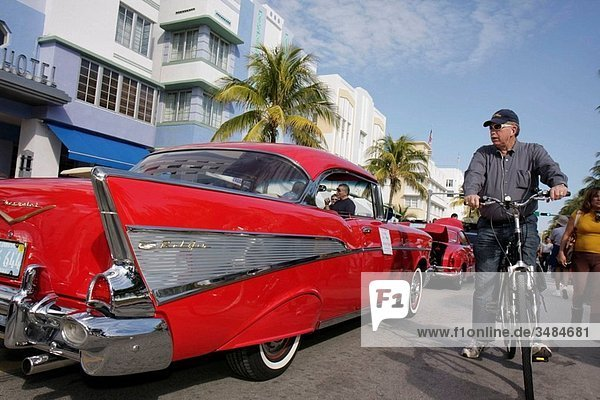 Florida  Miami Beach  ´Ocean Drive´  Art Deco Weekend  historic district  architecture  street festival  event  celebration  classic car  exhibit  palm tree  red  1957 Chevrolet  Bel Air  chrome fender  Hispanic  man  bicycle  hotels