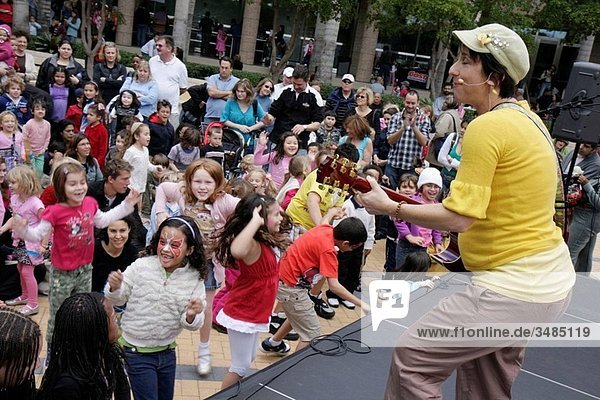 Florida  Miami  Adrienne Arsht Performing Arts Center  Free Family Fest  festival  performance  singer  performer  singing  musician  guitar  Shana Banana  audience  Hispanic  woman  boy  girl  child  parent  sing_a_long  dancing  dance  participation