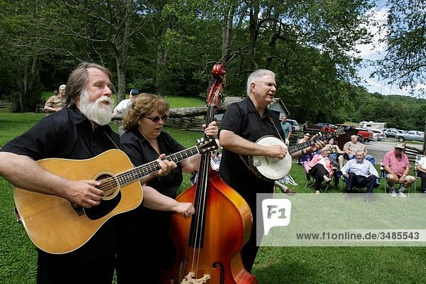 Virginia  Appalachian Mountains  Blue Ridge Parkway  All-American Road  National Scenic Byway  Mabry Mill  milepost 176  man  woman  trio  music  musicians  folk artists  outdoor concert  audience  guitar  bass  banjo  folding chair