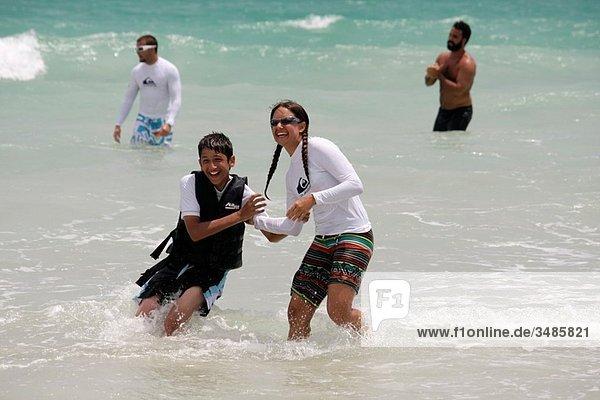 Florida  Miami Beach  South Beach  Atlantic Ocean  Recreation Department Surf Camp  high functioning autism  Aspergers  PDD-NOS  student  counselor  Hispanic  boy  woman  teen  surf  life jacket  vest  learn  coach  teach  fun  smiling