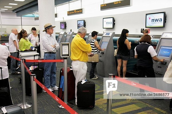 Florida  Miami  Miami International Airport  Northwest Airlines  NWA  carrier  ticket counter  line  queue  Black  man  woman  passenger  waiting  luggage  check-in kiosk  terminal