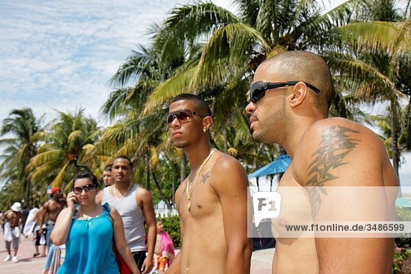 Florida  Miami Beach  ´Ocean Drive´  Urban Beach Week  Memorial Day Weekend  hip hop culture  Black  Hispanic  man  woman  young adult  sunglasses  bare chest  shaved head  pecs  tattoo  display  attract attention  sexuality