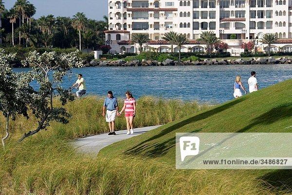 Florida  Miami Beach  South Pointe Park  Atlantic Ocean  Government Cut  urban public space  seashore  grass  vegetation  man  view of Fisher Island  luxury condominium  man  woman  holding hands  walking  walkway