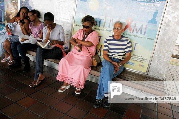 Florida  Miami  Metrorail  train  public transportation  rapid transit system  stop  station  commuter  Black  Hispanic  woman  man  girl  teen  mother  daughter  waiting  sitting  bench  read  reading  smart phone  wireless