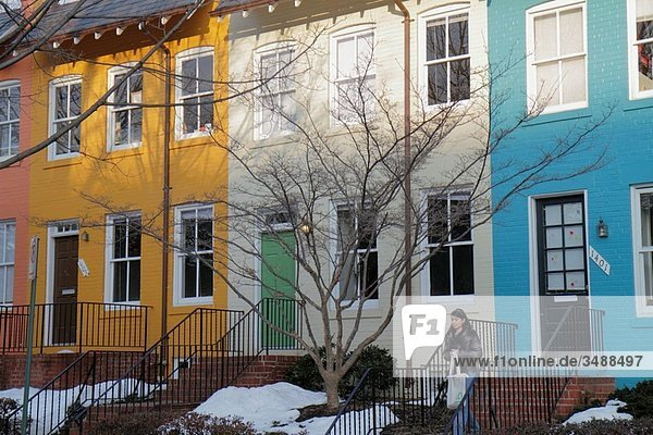 Washington DC  Georgetown  Prospect Street  historic neighborhood  rowhouse  college town  gentrification  Hispanic  woman  young adult  walking  sidewalk  colorful  snow