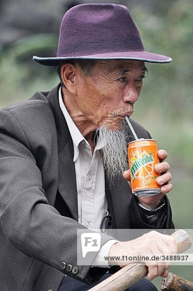 Tam Coc (Vietnam): a man drinking a soft-drink while paddling along the Ngo Dong river