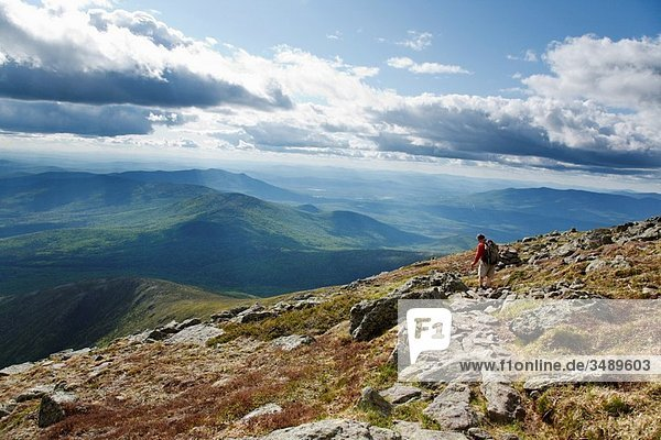 A hiker on the Appalachian Trail near Mount Clay during the summer months Located in the White Mountains  New Hampshire USA