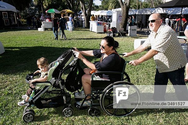 Florida  Miami  Coral Gables  University of Miami  Beaux Arts Festival of Art  juried show  community event  man  woman  boy  parent  child  father  mother  son  family  disabled  wheelchair  stroller  push  pushing