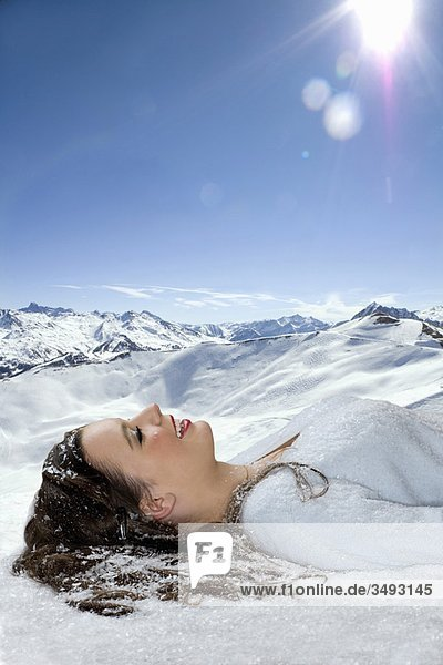 Junge Frau liegt im Schnee