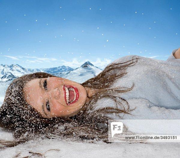 Lachende Frau liegt im gefallenen Schnee