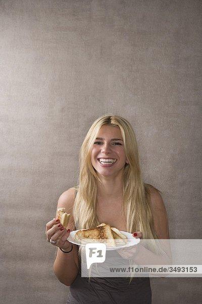 Junge Frau lächelt mit Sandwich