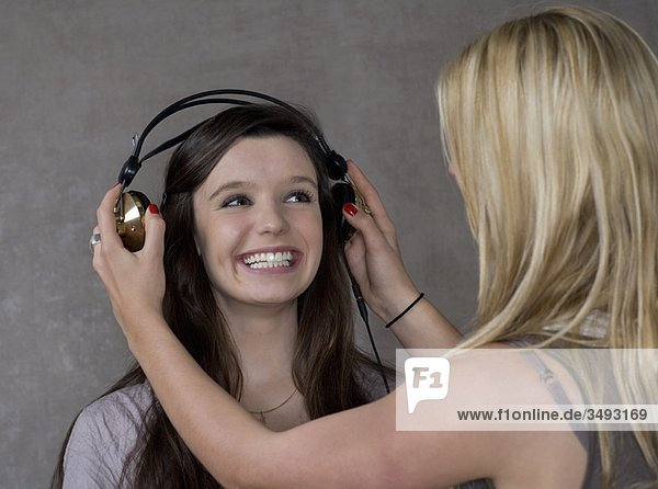 Teenager-Mädchen setzen Kopfhörer auf