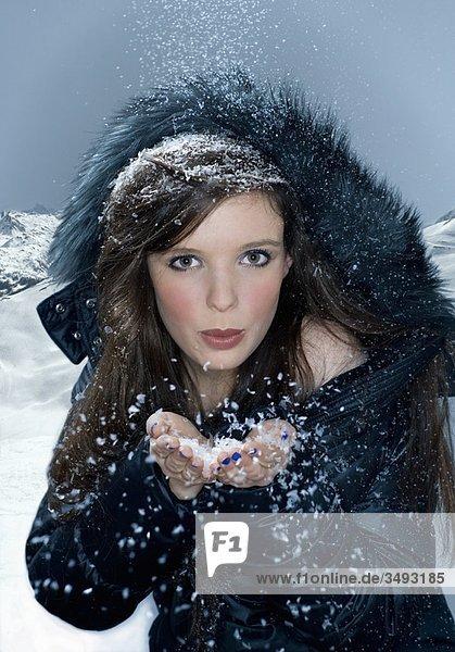 Frau bläst Schnee aus der Hand