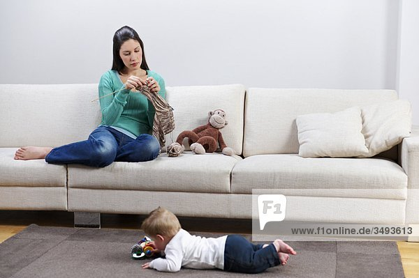 Woman knitting  baby playing on floor