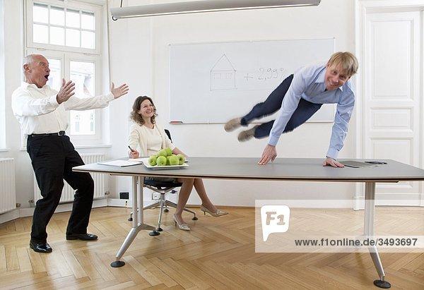 Geschäftsmann springt über den Tisch Geschäftsmann springt über den Tisch