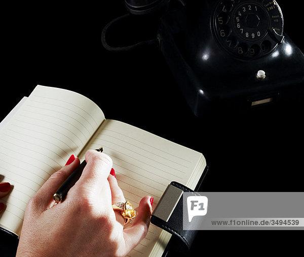 Frau schreibt in Notizbuch per Telefon
