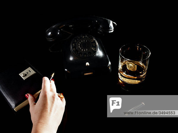 Female hand with notebook  telephone and glass of whiskey