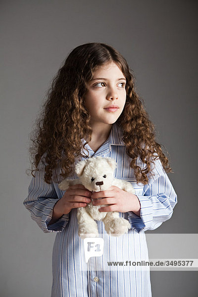 Junges Mädchen im Schlafanzug mit Teddybär