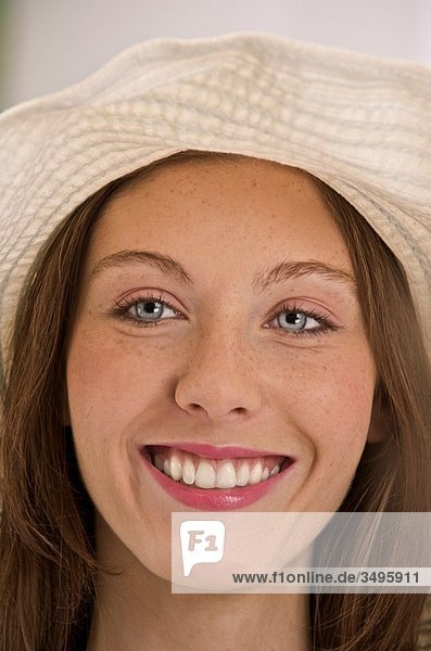 youngrelaxed and smiling suntanned woman with a sunhat